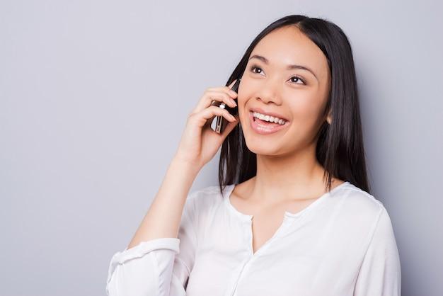 いい会話。携帯電話で話し、灰色の背景に立って笑っている美しい若いアジアの女性