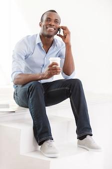 좋은 이야기. 파란 셔츠를 입은 쾌활한 젊은 아프리카 남자가 커피 한 잔을 들고 휴대전화로 통화를 하고 있다