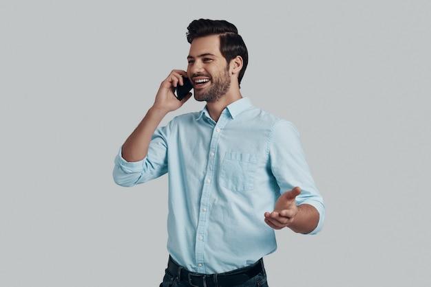 いい話。電話で話し、灰色の背景に立って笑っているハンサムな若い男
