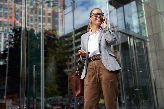 眼鏡と古典的な服を着て話す幸せなファッショナブルなビジネス女性の良い話の肖像画