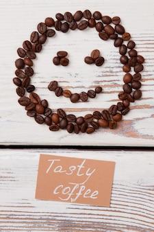 좋은 맛있는 커피 개념 평면 누워. 흰색 나무에 커피 콩의 미소.