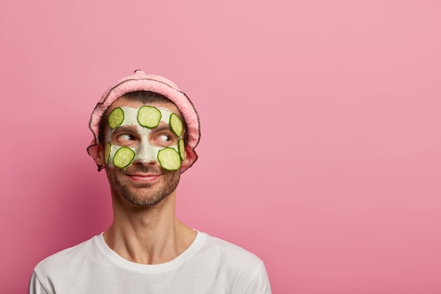 Good tempered happy man wears face mask and cucumbers, enjoys morning spa procedure, wants to look refreshed