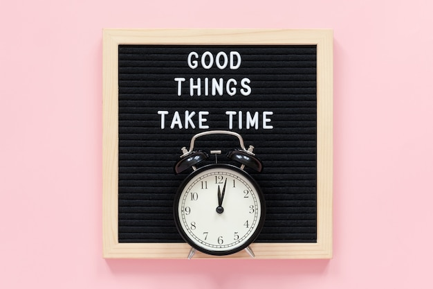 Good things take time. motivational quote on black letter board, black alarm clock on pink background. concept inspirational quote