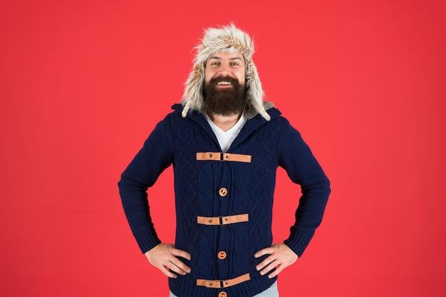 良い時間。男性のファッション。トレンディなヒップスターの笑顔。寒い季節のあごひげケア。残忍な男のイヤーフラップ帽子。ファーハットアクセサリー。冬の活動の準備ができているひげを生やした男。暖かく快適になります。