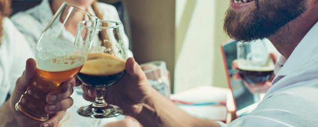 좋은 느낌. 맥주를 마시는 동안 친구, 동료의 손, 재미, 병 부딪치는 소리, 함께 안경.