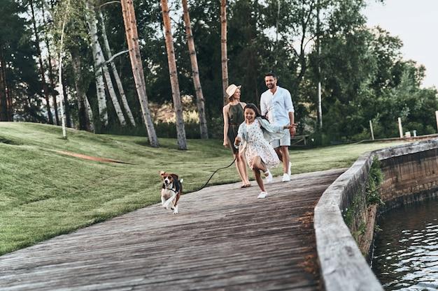 좋은 산책. 그녀의 부모가 뒤에 걷는 동안 강아지와 함께 달리고 웃는 귀여운 소녀의 전체 길이