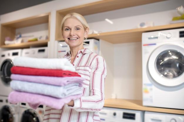 よく洗う。タオルの山を保持し、気分が良い金髪の女性の笑顔