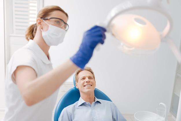 Хороший и мудрый квалифицированный врач делает оборудование более удобным перед началом процедуры и ее пациентом, ожидающим ее в кресле.