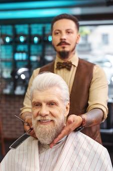 Хорошая работа. довольный клиент, выражающий позитив и сидя на стуле парикмахера
