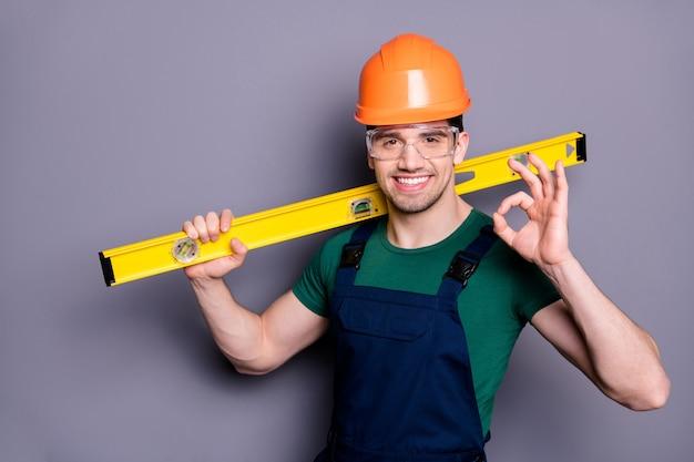 Хорошая работа! фото красивого лесоруба, опытного инженера, измерить стойку, выставить счетчик, символ окей, носить футболку, защитный комбинезон, шлем, очки, изолированные
