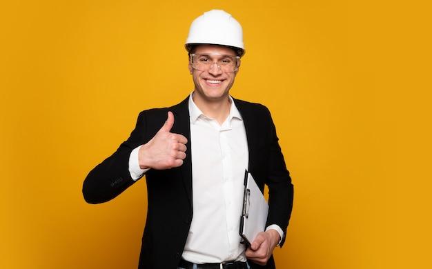 よくできました!スーツとヘルメットをかぶった前向きな職長が、メモを持って笑っている間、カメラを見て親指を立てています。
