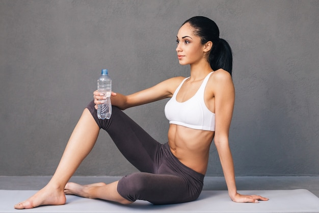 좋은 몸을 위한 좋은 운동. 회색 배경에 운동 매트에 앉아 물 한 병을 들고 멀리 바라보는 운동복을 입은 아름다운 젊은 아프리카 여성의 측면