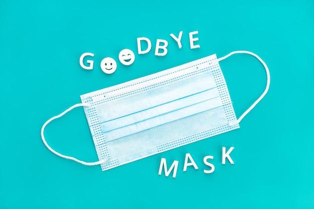さようならマスクフレーズと青い背景で隔離のフェイスマスク。フェイスマスクを着用する必要がなくなったというコンセプト