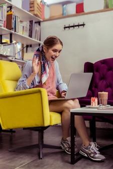 Вкусности впереди. положительная счастливая девушка, имеющая видеозвонок на своем ноутбуке и поднимающая руку в приветственном жесте