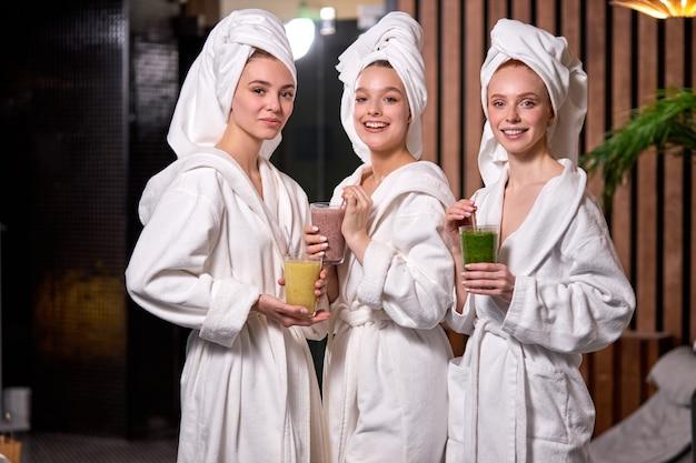 잘 생긴 여성은 뷰티 살롱에서 스파 트리트먼트를받는 동안 건강한 음료를 마시고 있습니다.
