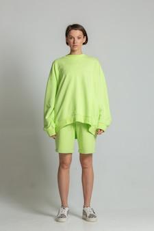 緑のスウェットシャツとショートパンツでフルハイトポーズをとる格好良い若い白人女性