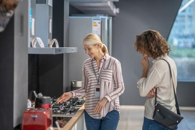 주방 용품. 여성 고객에게 상품을 보여주는 스트라이프 셔츠의 판매 도우미
