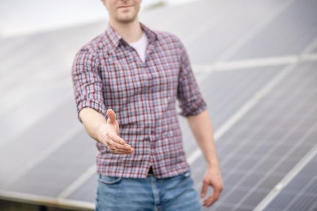 のれん。屋外の灰色の表面の前で挨拶で手を差し伸べるカジュアルな格子縞のシャツの男、顔は見えません