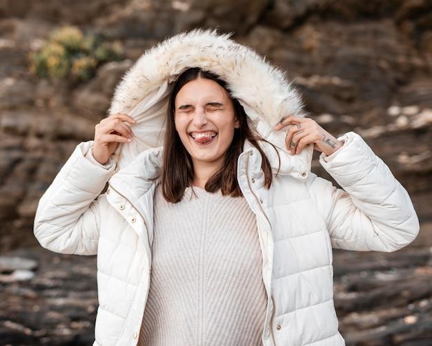 Тупая женщина на пляже в зимней куртке