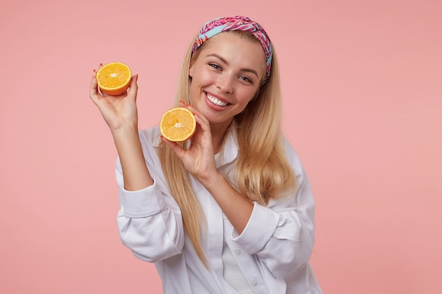 Goog cercando yound donna bionda in posa con metà arancione nelle sue mani, sorridendo allegramente, indossando la fascia colorata e una camicia bianca