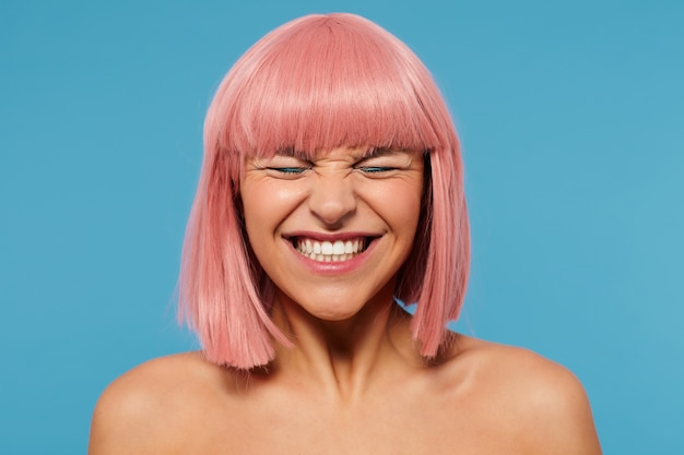 Goog looking young cheerful lovely pink haired female with bob haircut frowning her face while smiling widely, keeping eyes closed while posing over blue background
