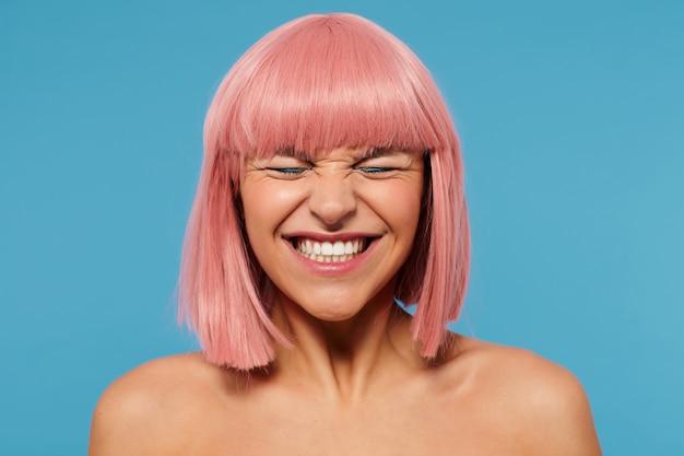파란색 배경 위에 포즈를 취하는 동안 눈을 감고 넓게 웃고있는 동안 그녀의 얼굴을 찌푸린 밥 이발로 젊은 쾌활한 사랑스러운 분홍색 머리 여성을 찾고있는 goog