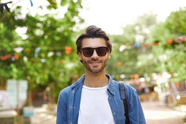 Гуг выглядит молодой темноволосый мужчина с бородой в повседневной одежде и солнцезащитных очках, стоящий над зеленым парком в солнечный теплый день, концепция положительных эмоций