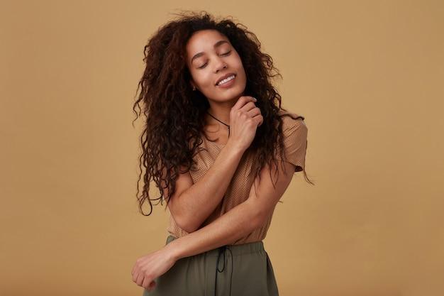 Goog cerca giovane donna dalla pelle scura riccia dai capelli castani felice che tiene gli occhi chiusi mentre sorride piacevolmente e la abbraccia con le mani alzate, isolate su beige