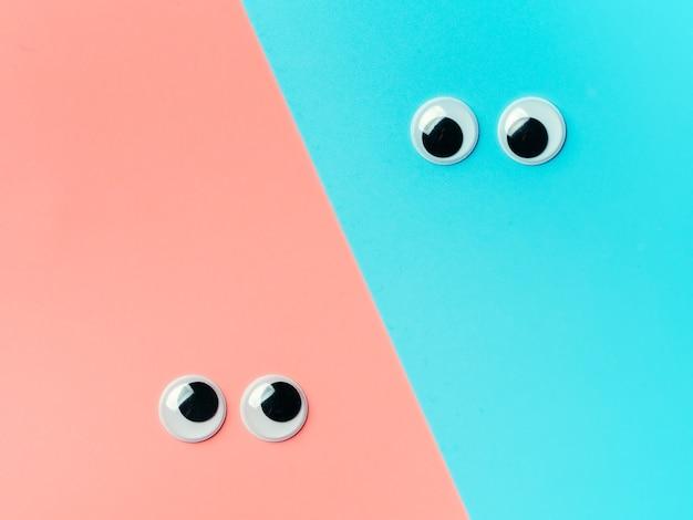 青とピンクの背景のぎょろ目。トップビューまたはフラットレイアウト。背景色が水色にプラスチックのおもちゃの目
