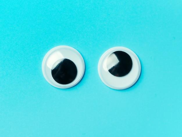 青の背景にぎょろ目。トップビューまたはフラットレイアウト。背景色が水色にプラスチックのおもちゃの目