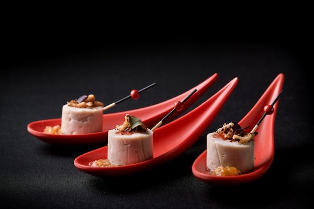 Паштет из гусиной печени, фуа-гра, подается на черном камне в японских красных ложках. паста с джемом и орехами