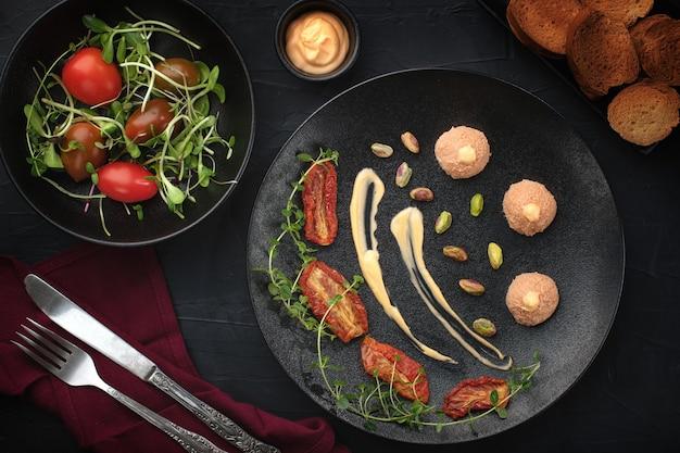 Гусиный паштет на черной тарелке, подается с вялеными помидорами на черном столе. .пластинчатая художественная композиция.