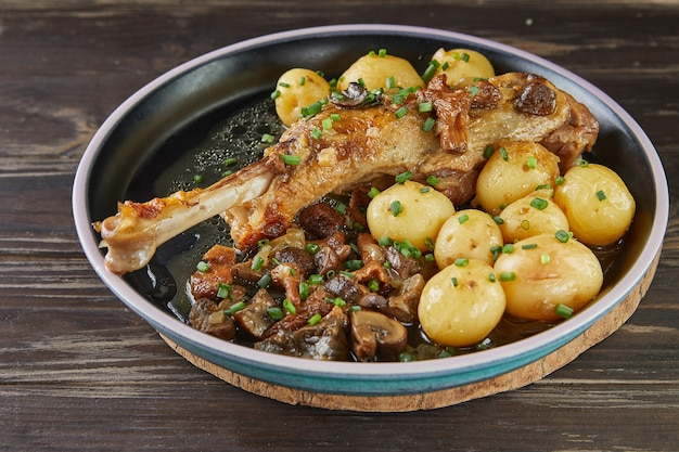 新しいジャガイモとアルマニャックで焼いたポートベローと森のキノコを添えたガチョウのシャンク。フランスのグルメ料理