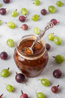 Gooseberry jam in a jar with fresh gooseberry berries on a gray surface