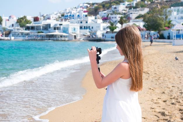 Маленькая девочка на пляже с камерой gopro делает фото