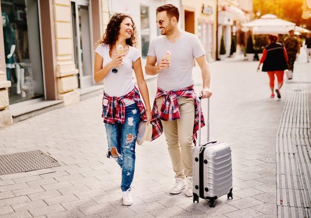 Goreous брюнетка девушка и бородатый мужчина, прогулки по городу во время еды мороженое.