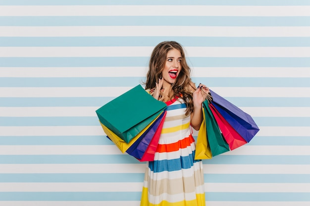 Gorgeos, stylish, young woman posing with colorful shopping bags. dark-haired blue-eyed lady with happy smile on light wall