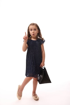 Gorgeous adorable 4 years old little caucasian european girl wearing evening attire, hold a shopping black packet and point on a copy space on white background. concept of black friday