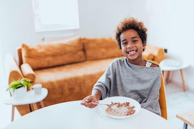 Gorgeous african american little girl eating cereals, looking at camera.