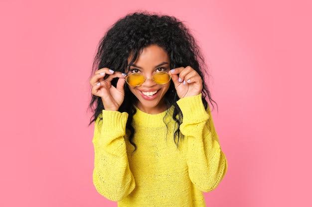 黄色いセーターと黄色いメガネをかけたゴージャスなアフリカの民族の女の子が横顔でポーズをとっています。彼女の頭はカメラの方を向いて、大きく笑っています。