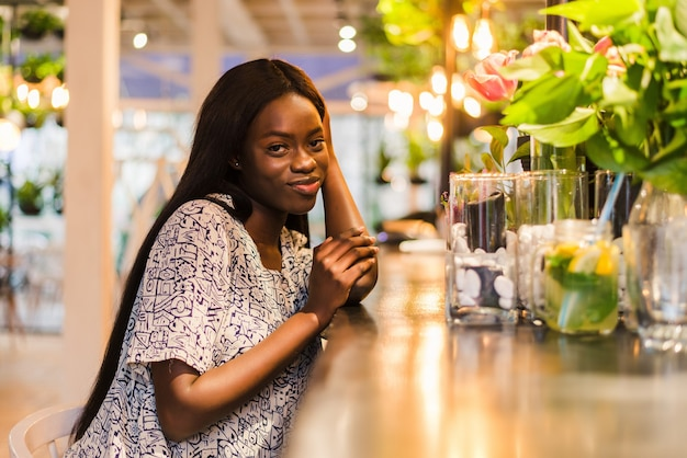 카페에 앉아 레모네이드를 마시는 화려한 아프리카 여자.
