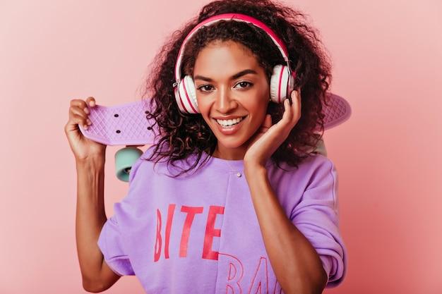 스케이트 보드 미소와 함께 화려한 아프리카 여자입니다. 핑크에 고립 된 헤드폰에 낭만적 인 곱슬 소녀의 실내 초상화.