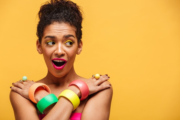 Gorgeous afro american woman in colorful adornment embarrassing while posing on camera half-naked with crossed hands on shoulders, over yellow copy space