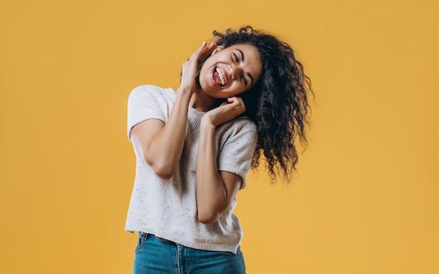 Великолепная афро-американская женщина слушает музыку в наушниках и подписывает на желтом фоне. очаровательная девушка в футболке и наушниках танцует с закрытыми глазами.