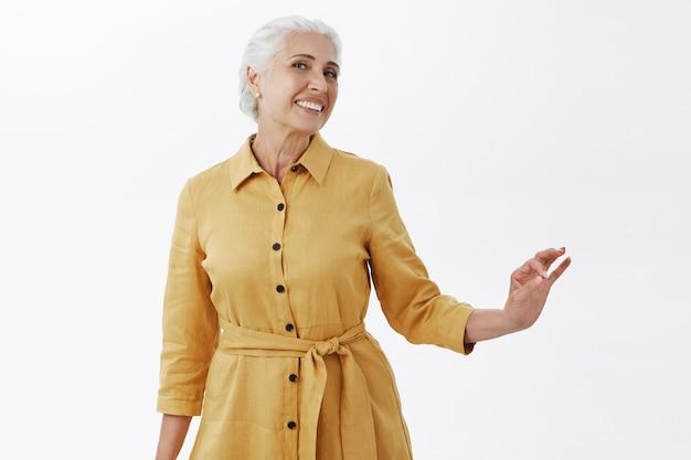 Великолепная и элегантная бабушка с удовольствием улыбается на белом фоне