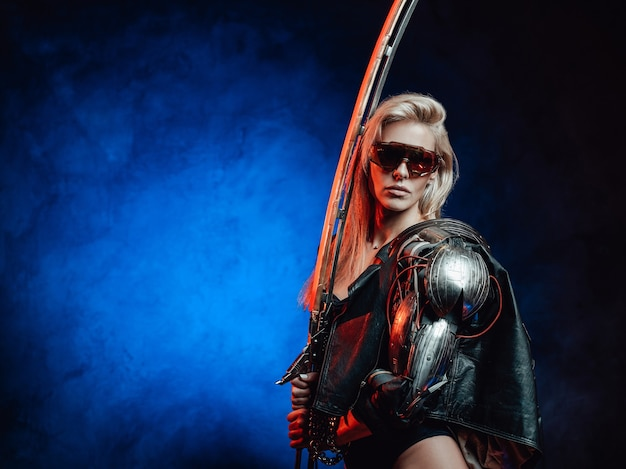 ブロンドの髪と未来からの剣を持つゴージャスで魅惑的な女性戦士は、暗い背景でポーズをとります。