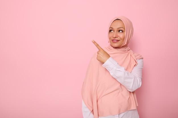ピンクの背景を見て、テキストのコピースペースを示す人差し指を指しているヒジャーブで覆われた頭を持つゴージャスなアラブのイスラム教徒の女性。宗教的な美しい女性とのビジネスコンセプト