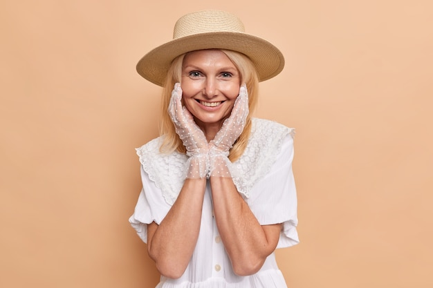 Gorgeous aristocratic woman with fair hair wears fedora white dress and lace gloves keeps hands on cheeks smiles pleasantly isolated over beige wall