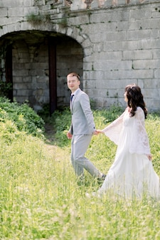 Gorgeous asian wedding couple holding hands walking on a background of the old castle.