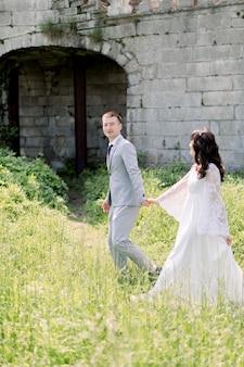 오래 된 성곽의 배경에 걷고 손을 잡고 화려한 아시아 웨딩 커플.